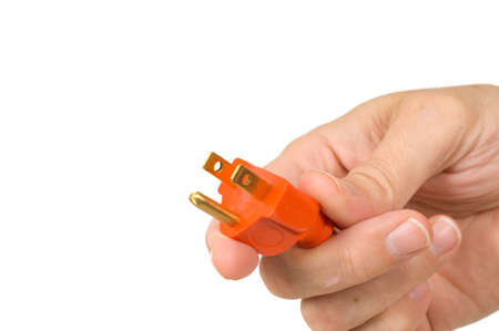 plugged: A mans hand holding the end of a new orange extension cord on a white background, symbol for connection or getting connected or plugged in