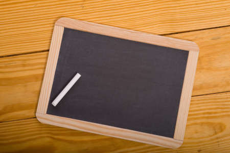 slate board: A blank school chalkboard or slate on a wood panel background with  a piece of white chalk, with copy space Stock Photo