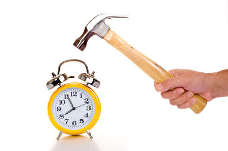 a hand holding a black mallet or hammer about to crush an old fashioned yellow alarm clock on a white background, time concept photo