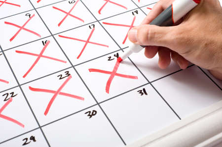 A hand holding a dry erase marker xing days of the month off of a calendar.  Passing of time conecpt.   Stock Photo