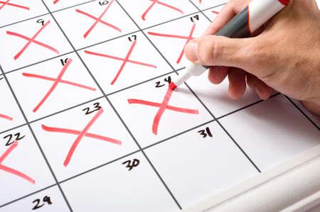 calendrier jour: Une main tenant un s�che effacer marqueur x'ing jour du mois � partir d'un calendrier. Passage du temps conecpt.