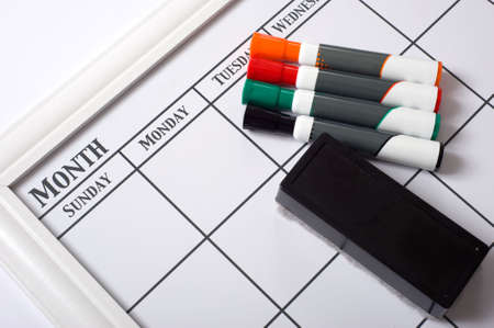 dry erase: Blank white calendar with dry erase markers and an eraser