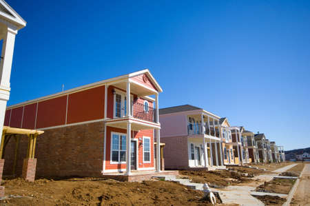 A row of new brightly colored traditional styled homes under construction  Stock Photo