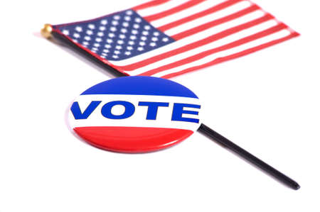 paper pin: A VOTE button lying on top of an American flag on a white background,  Election day symbols for the United States of America