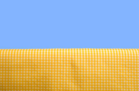 A yellow gingham or checked tablecloth background on a blue sky background