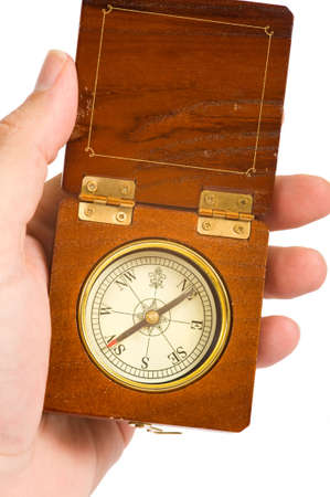 A hand holding a wooden compass with copy space