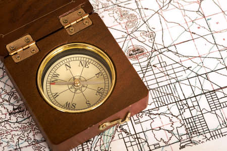 An old wooden compass lying on top of a topographical map