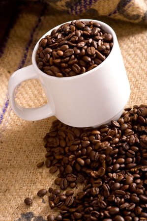 A white cup full of roasted coffee beans on a burlap coffee bean bag.  Background with copy space  Stock Photo - 4722833