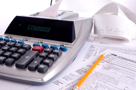 adding: An adding machine or calculator with adding machine tape or paper and tax forms Stock Photo