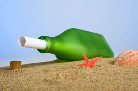 recieve: A rolled piece of paper in a green bottle on a sandy beach with sea shells etc, message in a bottle concept Stock Photo