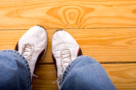 A man or boy with a pair of athletic shoes standing or sitting on a wood floor with copy space Stock Photo - 4726000