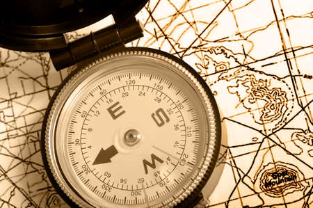 topographical: A compass lying on top of a topographical map- brown duotone or sepia Stock Photo