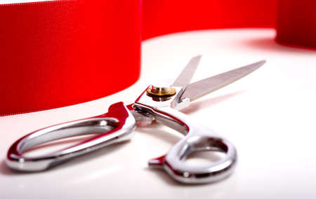 A red ribbon with a pair or shiny silver ceremonial scissors or sheers