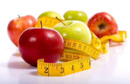 Several varieties of fresh apples on a white background with a tape measure.  Dieting and healthy eating concept.  Includes copy space Stock Photo