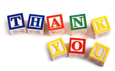 A childs alphabet blocks on a white background spelling out the words thank you