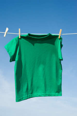 Individual t-shirts on a clothesline in front of a beautiful blue sky.  Add text or graphics to shirts, copy space Stock Photo - 4725899