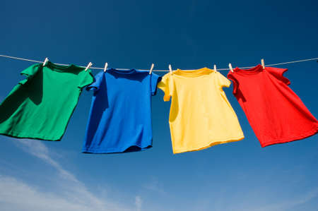a set of primary colored T-shirts hanging on a clothesline on a beautiful, sunny day, add text or graphic to shirts or copy space Imagens