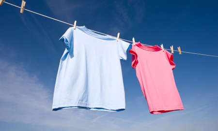 add text: a pink and a baby blue T-shirt hanging on a clothesline on a beautiful, sunny day, add text or graphic to shirts or copy space