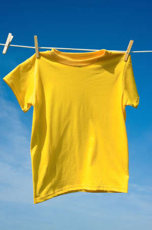 add text: A yellow colored T-shirts hanging on a clothesline on a beautiful, sunny day, add text or graphic to shirts or copy space