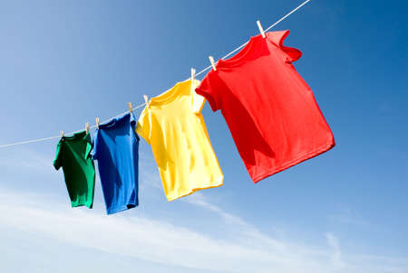 a set of primary colored T-shirts hanging on a clothesline on a beautiful, sunny day, add text or graphic to shirts or copy space 免版税图像