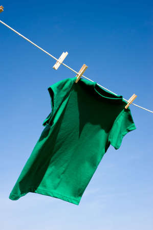 add text: A green colored T-shirts hanging on a clothesline on a beautiful, sunny day, add text or graphic to shirts or copy space