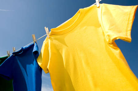 add text: a yellow and blue colored T-shirt hanging on a clothesline on a beautiful, sunny day, add text or graphic to shirts or copy space