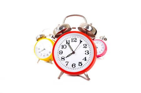 Several brightly colored traditional alarm clocks thrown on a white background photo