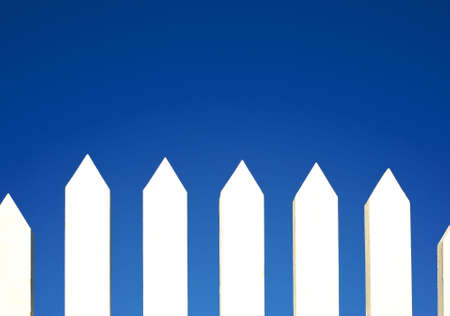 A white picket fence background in front of a bright blue sky with copy space. Stock Photo - 4725381