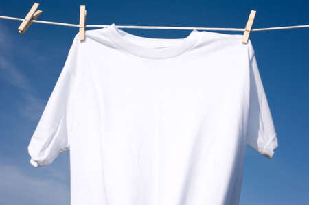 A plain white T-shirt hanging on a clothesline on a beautiful, sunny day, add text or graphic to shirts or copy space 免版税图像