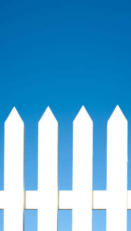 A white picket fence background in front of a bright blue sky with copy space. Stock Photo - 4725372
