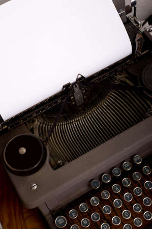 An antique, vintage typewriter with a blank piece of paper for message or copy, image includes keyboard and carriage photo
