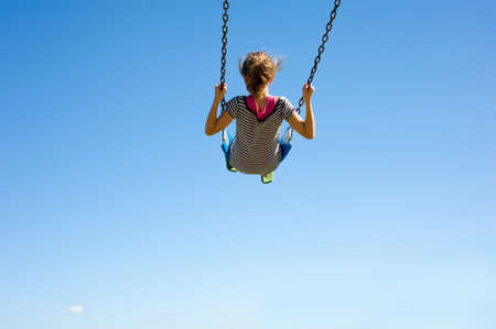 swing seat: A young girl playing on a swingset in front of a blue sky.  Girl is swinging very high in swing, with copy space Stock Photo
