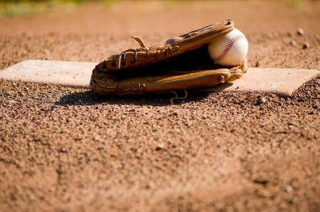 guante de beisbol: Un guante de b�isbol de cuero marr�n y una pelota de b�isbol de cuero blanco en mont�culo de un lanzador en un campo de b�isbol, con espacio de copia