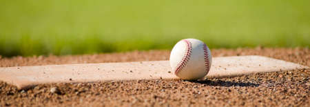 A white leather baseball lying on top of the pitchers mound at a baseball field with copy space