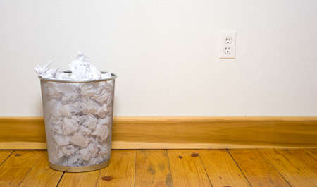 wire mesh: a wire mesh office trash can with crumpled paper on a wooden floor with a white wall, includes copy space Stock Photo