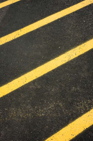 Black asphalt pavement painted with yellow stripes in a diagonal lines, with copy space