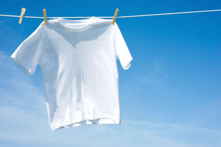add text: A plain white T-shirt hanging on a clothesline on a beautiful, sunny day, add text or graphic to shirts or copy space Stock Photo