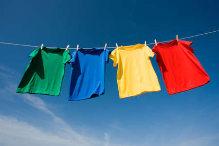 add text: a set of primary colored T-shirts hanging on a clothesline on a beautiful, sunny day, add text or graphic to shirts or copy space Stock Photo