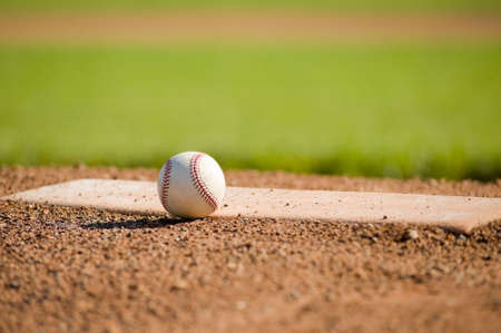 baseball diamond: A white leather baseball lying on top of the pitchers mound at a baseball field with copy space