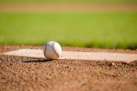 campo de beisbol: Una pelota de cuero blanco se extiende en la parte superior del mont�culo del pitcher en un campo de b�isbol con copia espacio