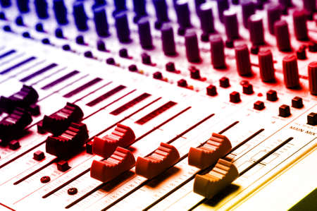 Audio recording equipment or soundboard background with many knobs and adjustments, board is a little dusty photo