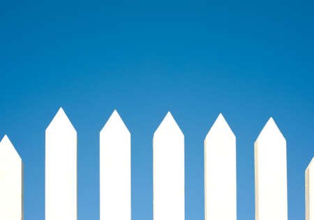 A white picket fence background in front of a bright blue sky with copy space. photo