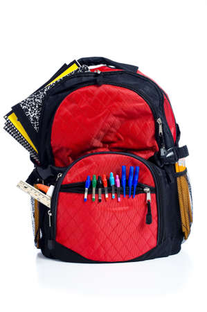 school backpack: A red school back pack or book bag overflowing with school supplies including, notebooks, pens, pencils, rulers and glue