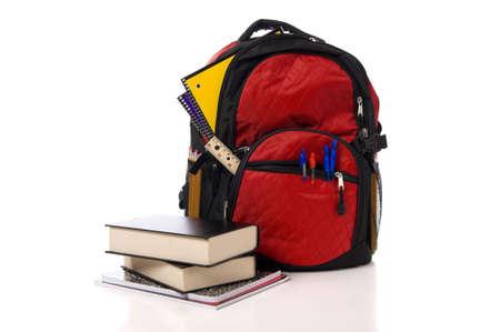 school backpack: Una mochila de color rojo desbordante escuela o bolsa de libros con los libros de texto sobre un fondo blanco