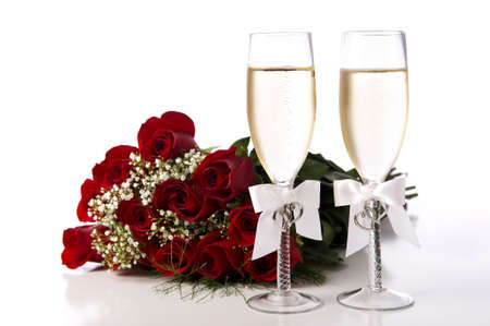 A bouquet of red roses and tow champange flutes or toasting glasses with champagne on a white background