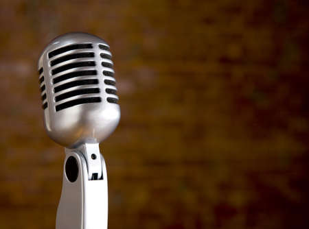 old items: A silver vintage microphone in front of a blurred red brick wall with copy space Stock Photo