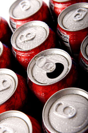 Cans of ice cold red soda pop in aluminum cans forming a background