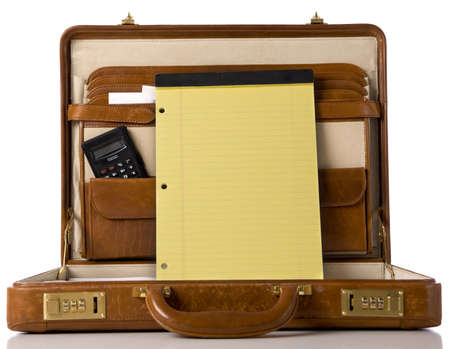 attache: A brown leather briefcase with a blank legal tablet with copy space.  Includes calculator etc.