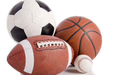 A group of sports balls on a white background, including a baseball, an American football, a basketball, and a soocer ball Stock Photo