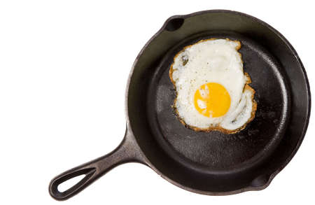 nourishment: A fried egg in a black iron skillet on a white background, food, nourishment concept